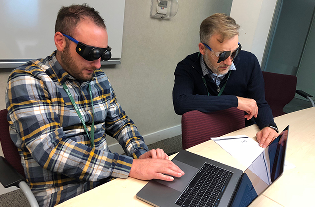 Image of one man wearing visual impairment simulation googles using a laptop, and another man wearing visual impairment simulation goggles looking at a sheet of paper