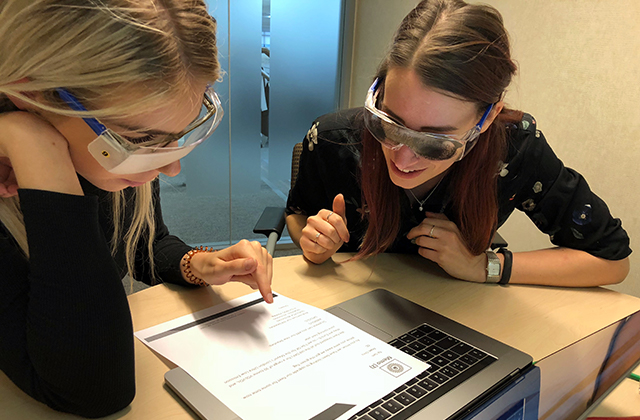 Image of two women wearing goggles that simulate visual impairments